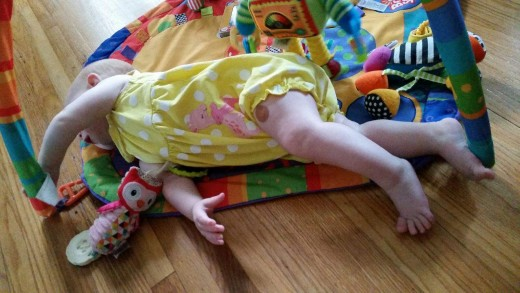 Reaching and rolling are fun and productive. Her mom places items just out of reach to encourage Imogen to roll.
