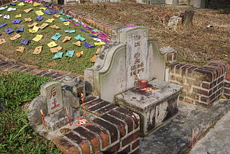 Brightly covered papers placed near a grave in Bukit Brown Cemetery, Singapore during the Qingming Festival.
