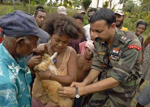 US Navy 070810-N-4954I-120 Lt. Col. Raveesh Chhajed, a veterinarian from the Indian Army, gives a family cat a rabies vaccination while onlookers gather to see the procedure
