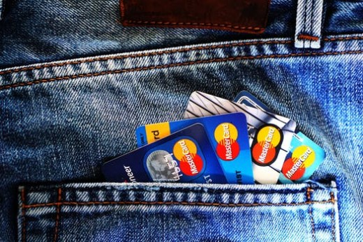 Lots of credit cards being shown from a man's back pocket.