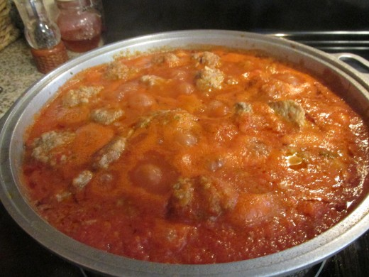 Pot of tomato sauce with meatballs.
