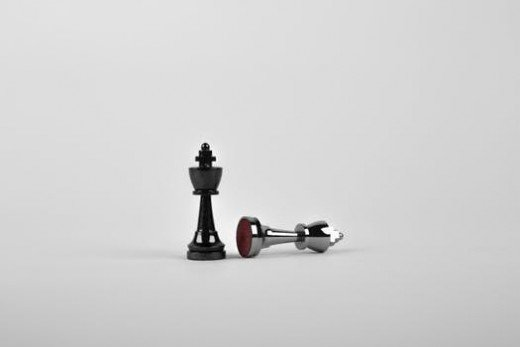 Chess pieces. The white piece has fallen, while the black piece remains standing up.