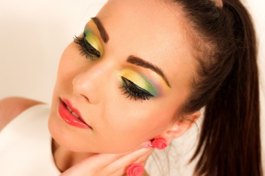 Young woman having fun with bright eyeshadow shades. Appearing lively and stylish.