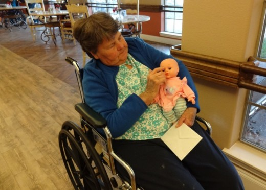 Norma finds comfort in taking her baby doll with her on her daily rounds at the skilled nursing facility.