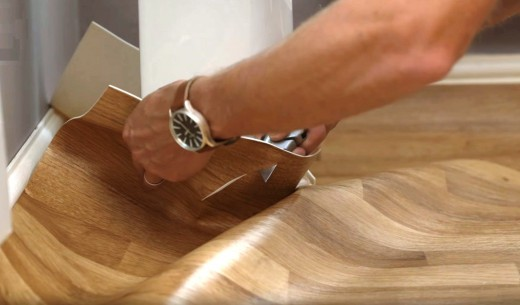 Cut a series of slits in the vinyl around the pedestal with a utility knife.