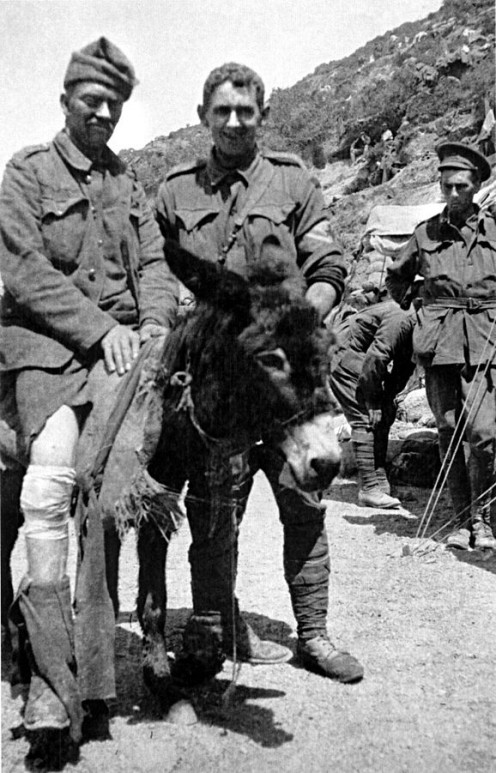Simpson (centre) with his donkey transporting a soldier with a leg wound heading to a medical post.