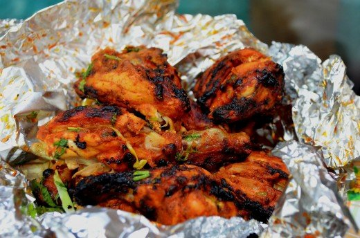 Keeping food wrapped during oven cooking prevents greasy splashes. Roast chicken tandoor-style cooked in aluminum foil parcels.