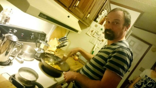 The author cooking a meal with a wok at a friend's house some years back. The wok is a remarkably versatile cooking pan, which can be used for stir fries, general frying, boiling, steaming, and stewing.