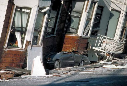 The third floor of this building is what crushed the car.  This was thanks to a combination of liquefaction and a soft first story.
