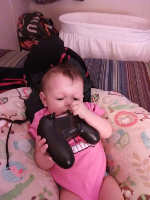 Now that she can be home, she loves playing with Daddy's PS4 controllers.