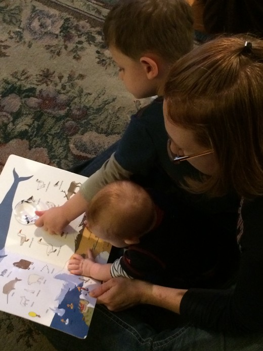 Ben is using a small magnifier to view the illustrations. Imogen enjoys the sound of her mother's voice and the colorful pages.