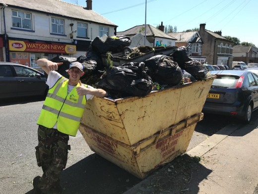 A volunteer stood by a skip