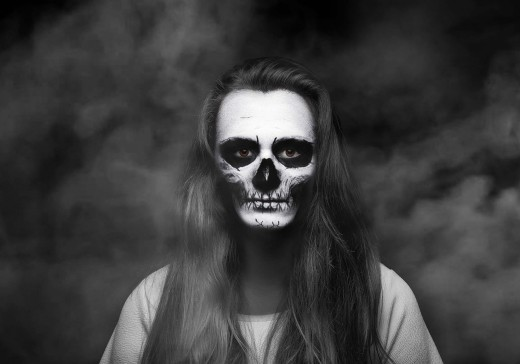A woman capitalizing on her long hair wearing a simple skull makeup application.