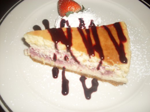 cheesecake with chocolate drizzle, whipped cream and strawberry