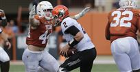 Brecklyn Hager shown making one of his many sacks against Oklahoma State quarterback.