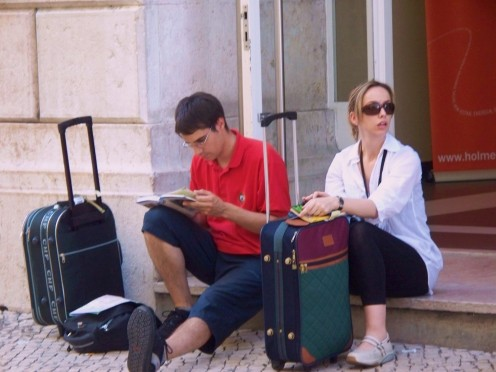 Without a plan, this couple arranges their stay in Lisbon, Portugal from th sidewalk.