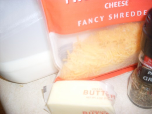 Whole milk, butter, shredded cheese and spices for preparing the ultimate cheesy potatoes dish