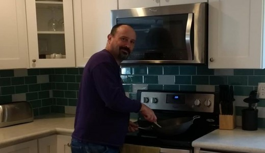 The author at the stove at home with a wok. The wok is a remarkably versatile cooking pan, which can be used for stir fries, general frying, boiling, steaming, and stewing.