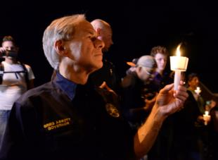 Texas Governor Greg Abbott participates in candlelight vigil near church where 26 were murdered Sunday.
