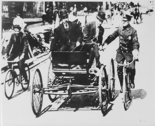 Traffic violator stopped by policeman in 1900 riding a bicycle.