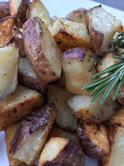 Crispy on the outside, fluffy and tender inside and fragrant with fresh rosemary and garlic, rosemary roasted potatoes are an easy and delicious recipe you'll use again and again!
