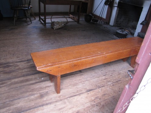 A vintage plank bench in a historic village.