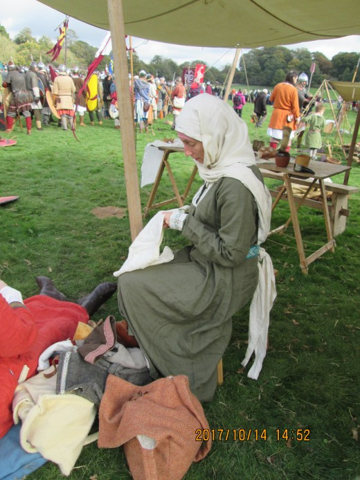 A tense time: patiently stitching in the entrance to her husband's tent, a wife awaits his return from the fight on 14th October, 1066.