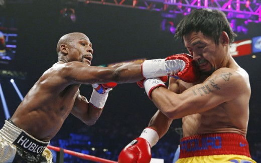 Floyd Mayweather gives a right hook to Manny Pacquiao