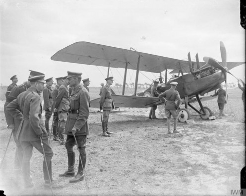 The Official Visits To the Western Front, 1914-1918 King George V with Brigadier General John Becke at the Bray-Dunes aerodrome, 5 July 1917. Edward, the Prince of Wales, is looking at a Royal Aircraft Factory R.E.8 biplane.