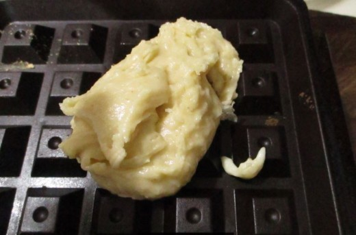 Glop of batter on center of waffle baker