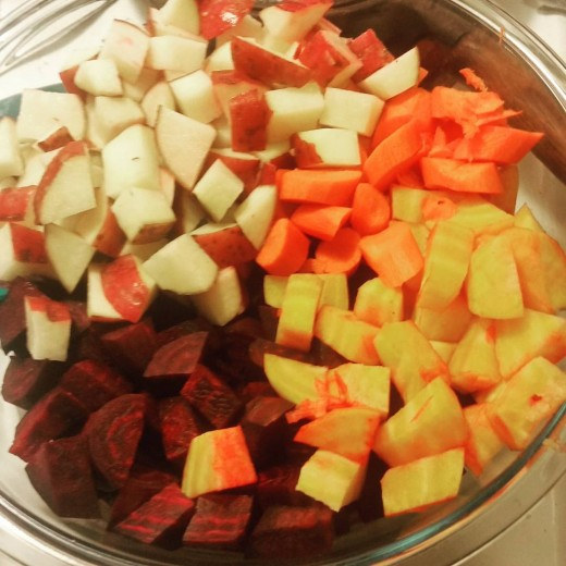 A large bowl filled with chopped up red beets, golden beets, orange carrots, and red potatoes.
