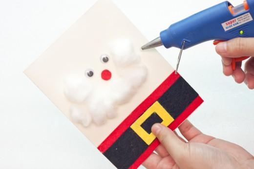 Glue the cotton balls onto your Santa card using your hot glue gun or craft glue.