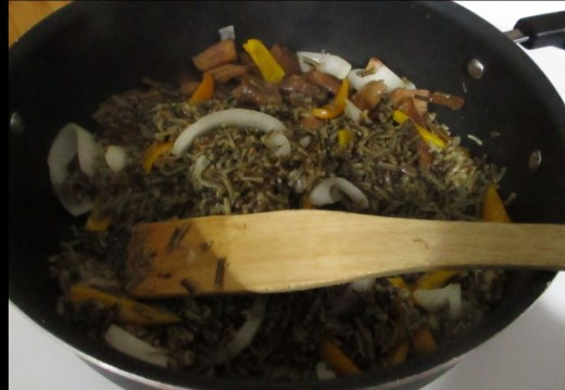 place butter in pan and add cooked rice and onions, peppers and mushrooms. Cook until onions are caramelized