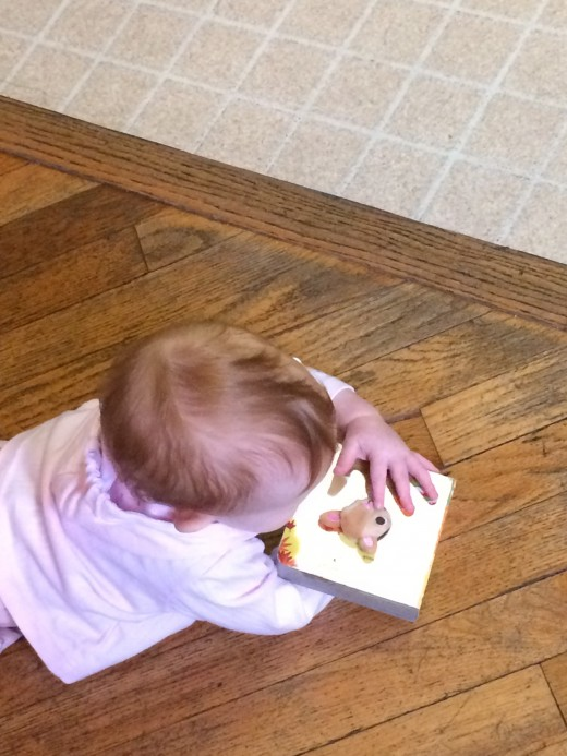 Imogen explores books on her own, as well as with others.