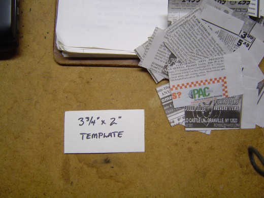 A simple cardboard template to cut newspaper strips with.