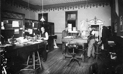 Three men working in a bank in a small town early in the twentieth century ( one is the grandfather of the author)