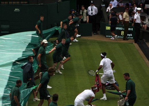 Rain stops play. Players grab and run as the covers come on at Centre Court.