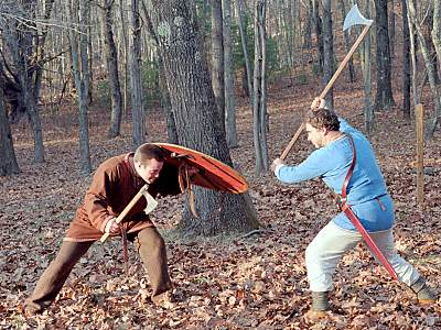 Learning to fight with axes. The man on the left has a hand axe and large, round shield. The man on the right has a long-handled Dane axe and no shield. Who, if anyone, has the advantage?
