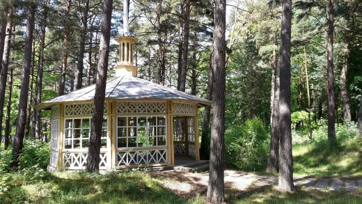 A wooden house and gazebo offers a quiet setting in a wooded area.