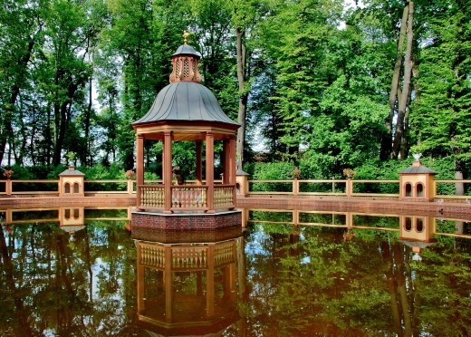 A gazebo with bridge placed at the edge of a pond surrounded by woodland landscaping for a picturesque site for visual relaxation and meditation.