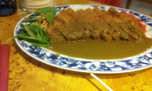 A Generous Serving Of Curry Sauce Is Added To The Breaded Pork In