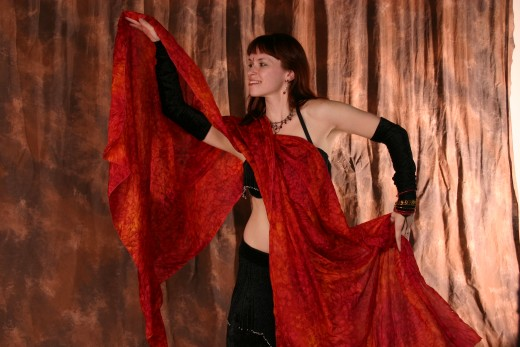 A cabaret belly dancer wearing a dramatic black costume working a long red veil to enhance romantic movements.