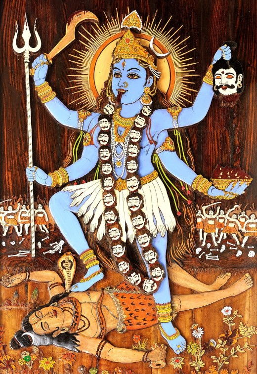 Kali is depicted as a naked, wild-haired black goddess with her tongue protruding from her mouth, dripping blood. She wears a necklace of skulls and earrings of dismembered corpses, standing with one foot on Shiva's chest.