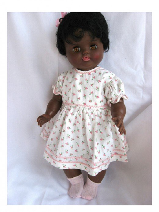 Topsy doll redressed in a vintage cotton dress with tiny pink rosebuds and trimmed in narrow pink rick - rack braid.