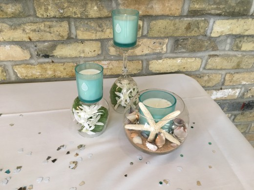 Place flowers in up-side-down wine glasses and put candles on top. Partially fill a glass bowl with sand, place a candle inside, decorate with small shells and stand a star fish in front of the candle!
