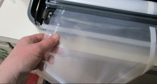 to remove bag, grasp the newly cut bag with your fingers.
