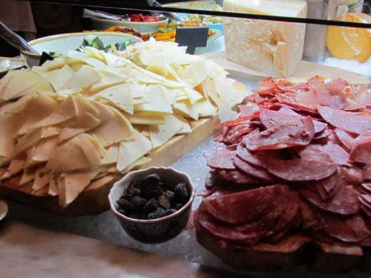 A variety of cheeses, meats, olives, spinach, lettuce and other choices exist on this outstanding buffet.