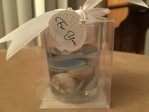 A small candle holder with shells secured in gel and a tea candle on top made a very nice party favor. No, I didn't make the party favors!