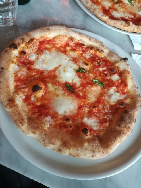 "A Neapolitan style ""pizza margherita"" topped with tomato and mozzarella, cooked into wood oven."