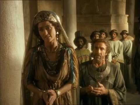 Esther speaks to the King while Mordechai watching from behind